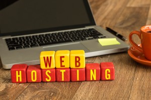 Web Hosting written on a wooden cube in a office desk